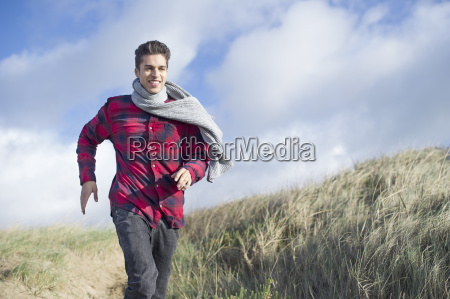 young man running on sand dunes