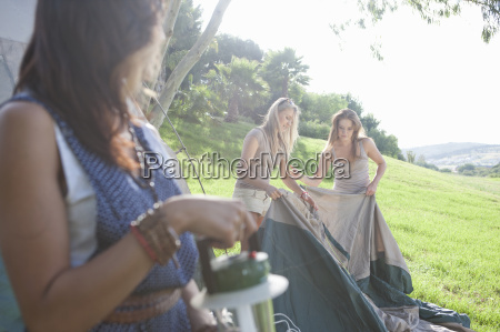 three young female friends preparing tent
