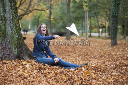 young woman throwing paper plane in