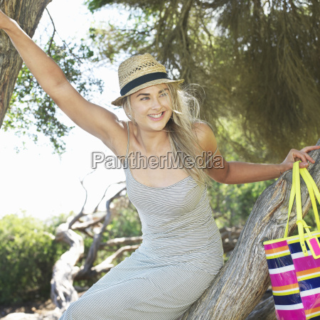 young woman sitting on tree branch