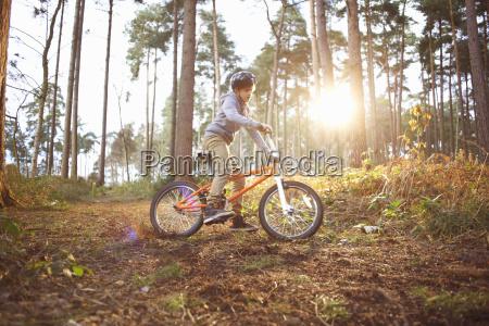 boy riding his bmx bike through