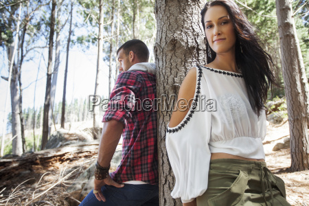 young couple leaning against tree in