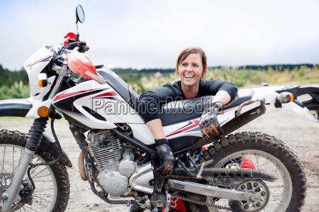 portraet von laechelnder junger erwachsener motorradfahrerin