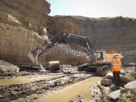 worker standing next to excavator inspecting
