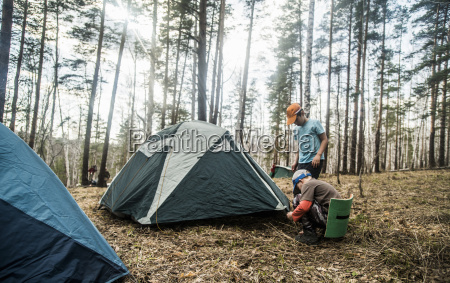 two boys preparing tent for forest
