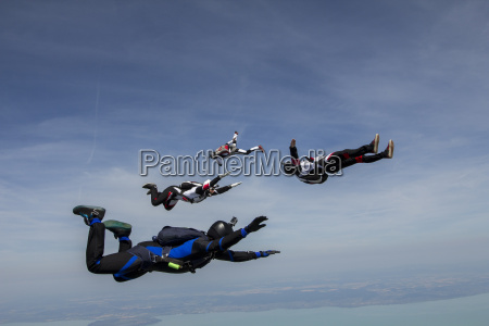 four young adult male skydivers free