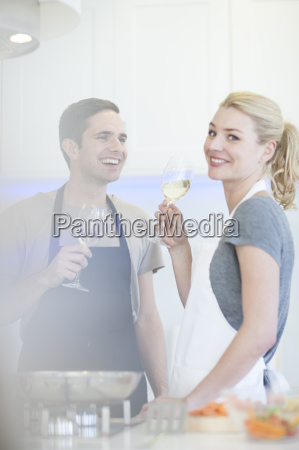 couple preparing food and drinking glass