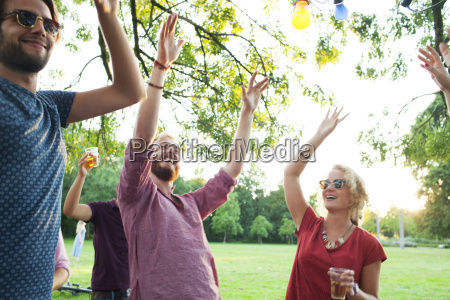 adult friends dancing with arms raised