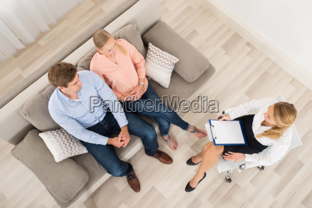 couple sitting on sofa with psychologist