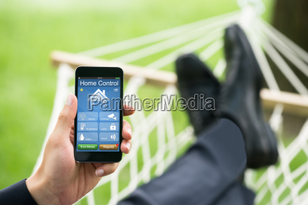 man with mobile phone showing home