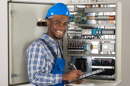 maennlicher techniker holding clipboard