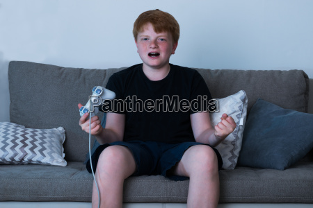junge sitzt auf dem sofa videospiele
