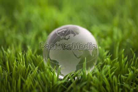 kristallkugel auf gruenem gras weltumweltkonzept