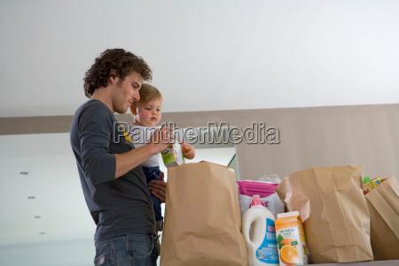 vater und kind mit einkaufstueten
