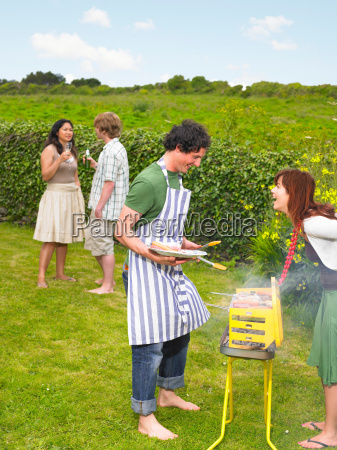 young man tending barbecue with friends