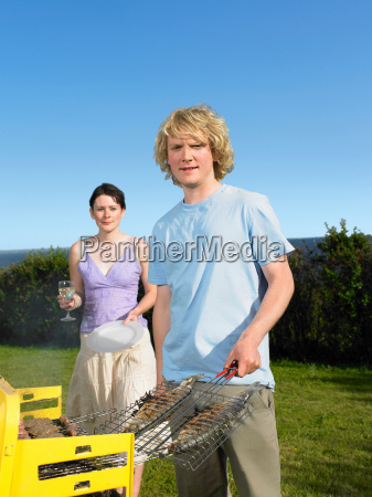 man with two barbecued fish