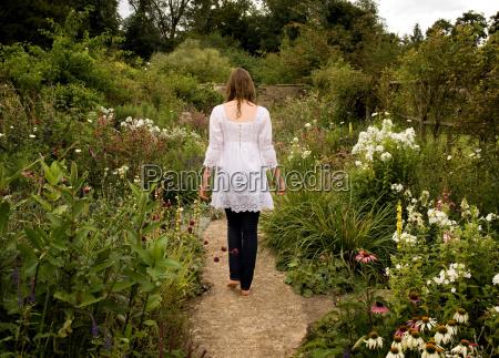 a female walking through a garden