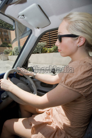 young woman driving electric car