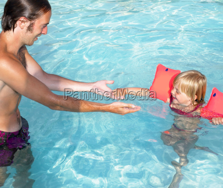 father teaching daughter how to swim