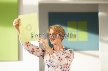 woman looking at recycling logo
