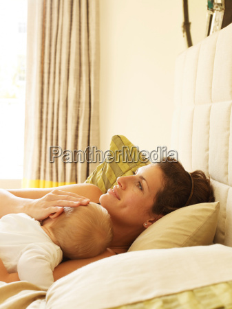 mother lying in bed with baby