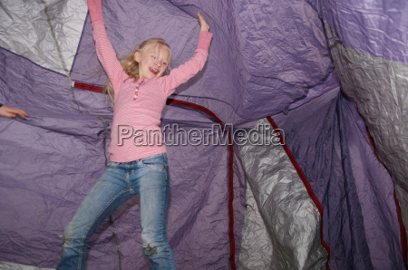 girl playing under tent