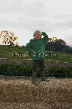 young boy on hay bales