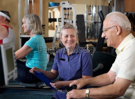 senior male at gym with instructor