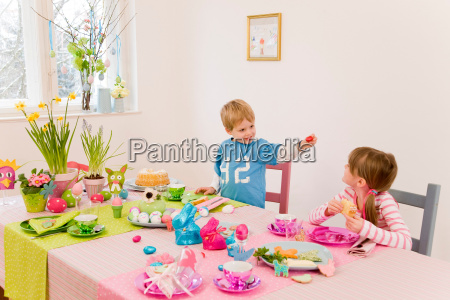 girl and boy admire easter table