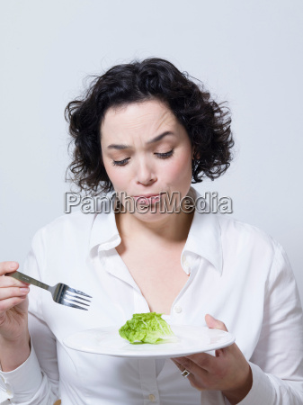 woman looking at a leaf of
