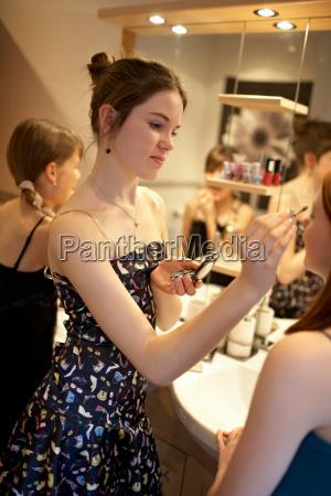 teenage girls applying make up