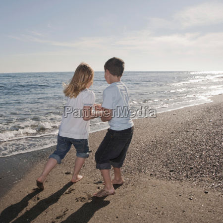 boy and girl running on beach