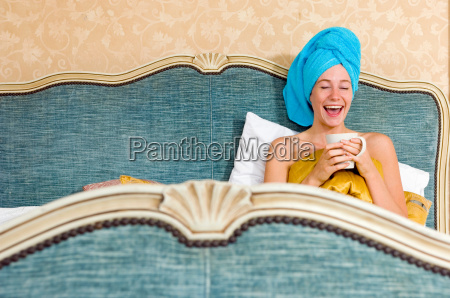 woman looking happy in bed with