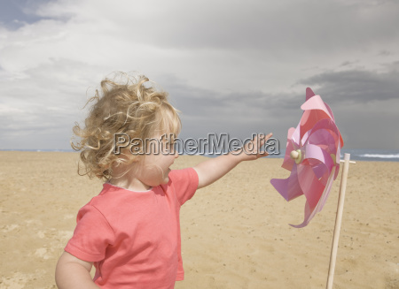 young girl with windmill on beach