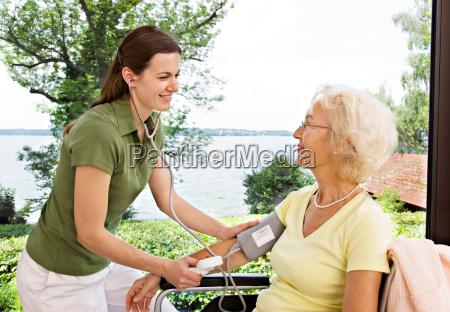 nurse taking womans blood pressure