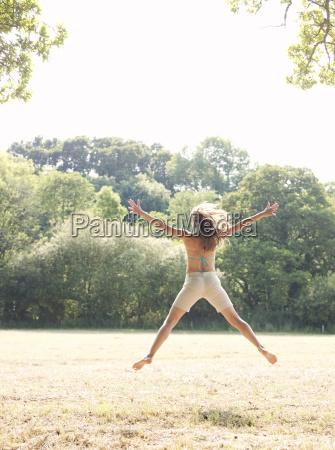woman in bikini jumping in country