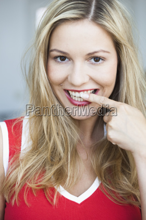 young woman pointing at her teeth