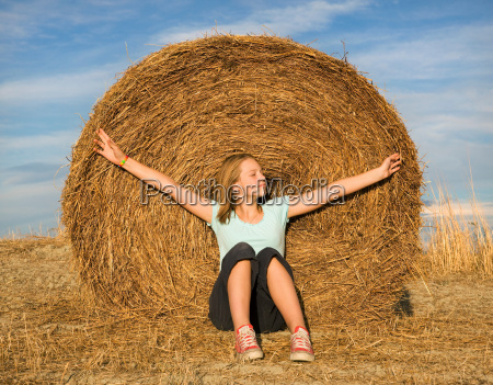 girl sitting in front of hay