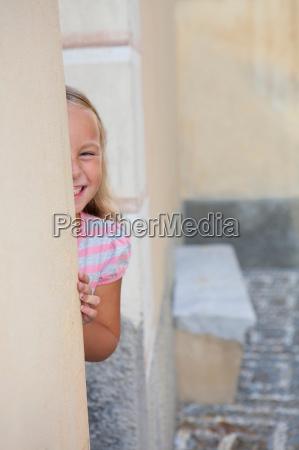 girl hiding behind wall laughing