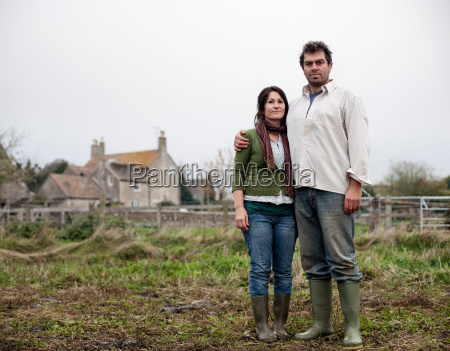 couple standing in front of farm