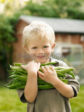 young boy holding garden produce outside