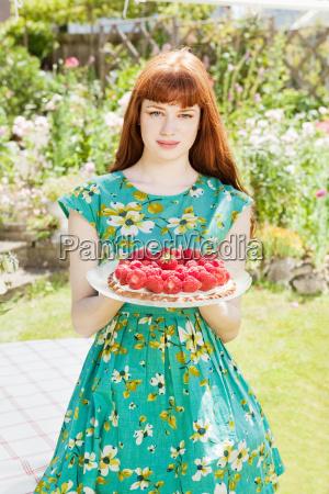 woman stands strawberry tart in garden