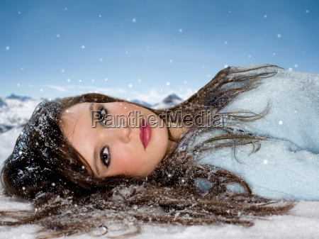 young woman lays in snow portrait