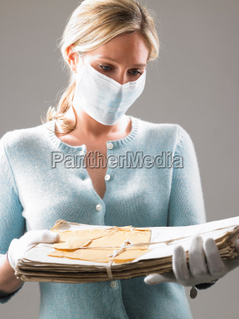 woman with mask holding precious files