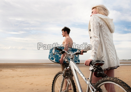 couple on beach with bike