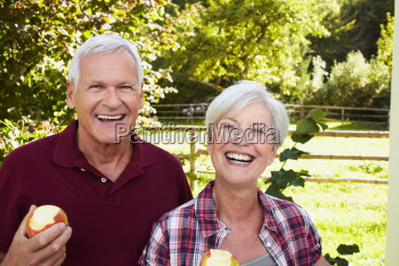 senior couple eating apples smiling