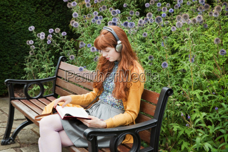 woman reading sitting on bench in