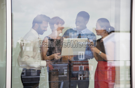 four business people using laptop