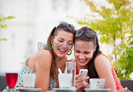 young women looking at phone in