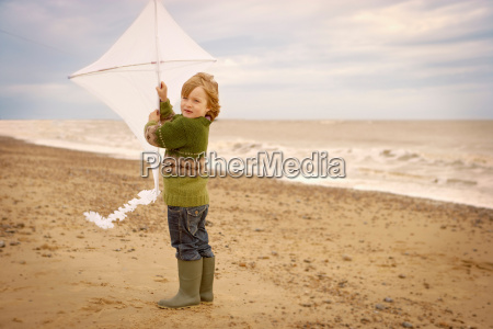 young boy on beach holding kite